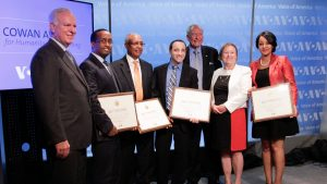 CEO John Lansing and others standing before Cowan Awards backdrop with awards