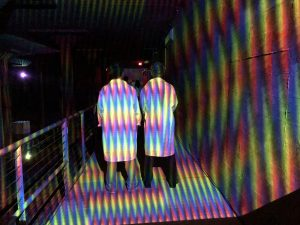 Two figures walk bathed in colored lights