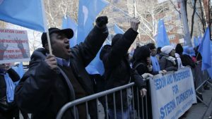 Protesters wave blue flags and stand behind a barricade
