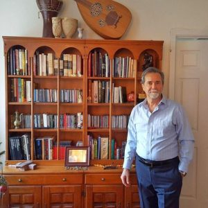 Nabeel Khoury poses in front of a bookshelf