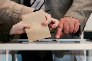 Two different hands with ballot over ballot box