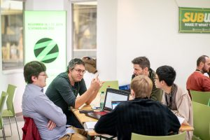 hackers sit around a table at Zoohackathon