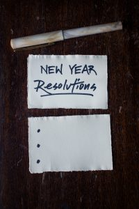 Pen and pad labeled new year resolutions