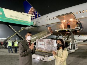 Aircraft with USAID relief packages andU.S. officials in foreground