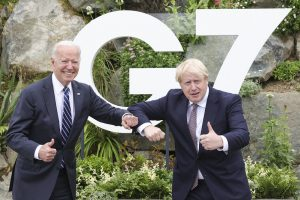 Pres Biden and PM Johnson in front of G7 sign
