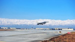 jet taking off with mountains in distance